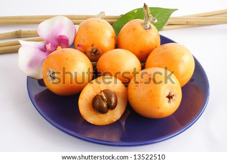 Blue plate with some fresh colorful loquats - stock photo