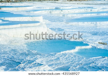 Blue pools and white travertine terraces at Pamukkale, Turkey  - stock photo