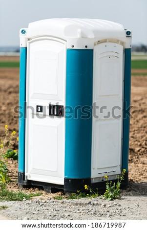 Blue portable mobile toilet  next to a construction site - stock photo