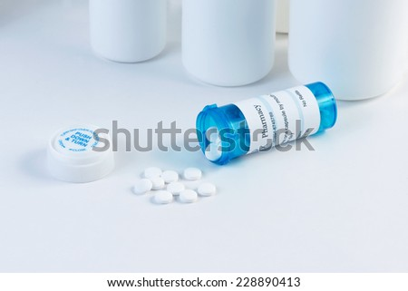 Blue prescription bottle with white pills and bottles in background. - stock photo