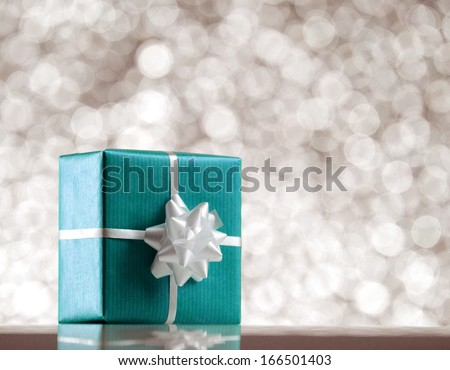 blue present box with white bow on bokeh light  background - stock photo