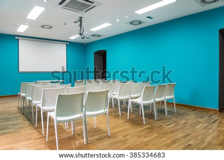 Blue presentation room with white chairs - stock photo