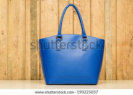 blue purse on wood background, luxury women accessory - stock photo