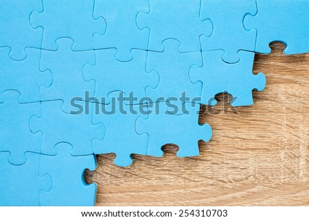 Blue puzzle on wooden background.Teamwork concept - stock photo