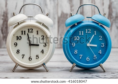 Blue retro alarm clock on white wooden background - stock photo
