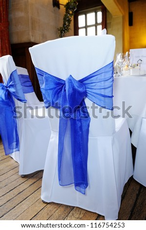 Blue ribbon chair cover tied in bow at wedding reception - stock photo