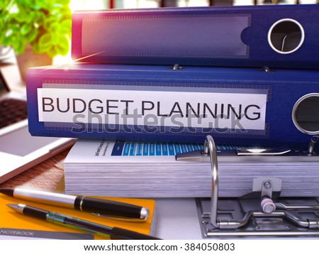 Blue Ring Binder with Inscription Budget Planning on Background of Working Table with Office Supplies and Laptop. Budget Planning Business Concept on Blurred Background. 3D Render. - stock photo
