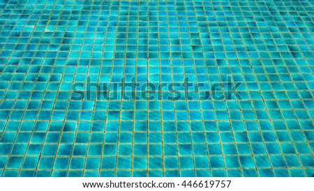 Blue ripped water in swimming pool with ceramic tile mosaic in background - stock photo