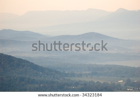 blue rolling hills at sunrise with fog - stock photo