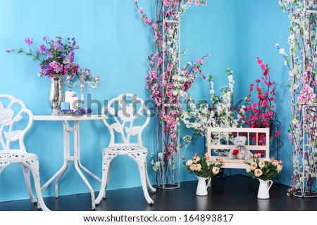 Blue room with retro table and chairs, decorated with flowers. - stock photo
