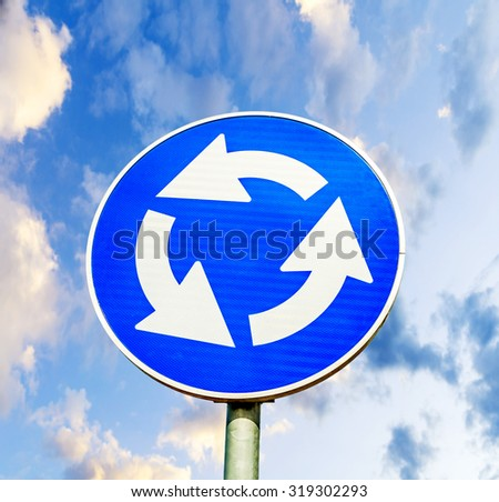 Blue roundabout crossroad road traffic sign against blue cloudy sky - stock photo