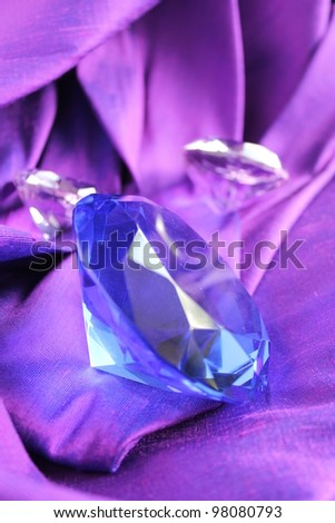Blue sapphire on purple silk - stock photo