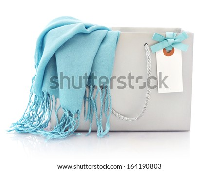 Blue scarf in shopping bag with tag isolated on a white background - stock photo