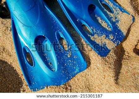 blue scuba fins in the beach sand - stock photo