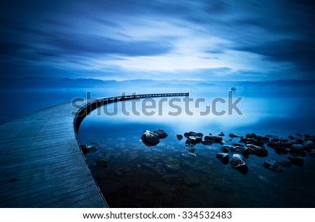Blue sea and curve jetty , long exposure photography. - stock photo