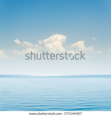 blue sea and sky with clouds over it - stock photo