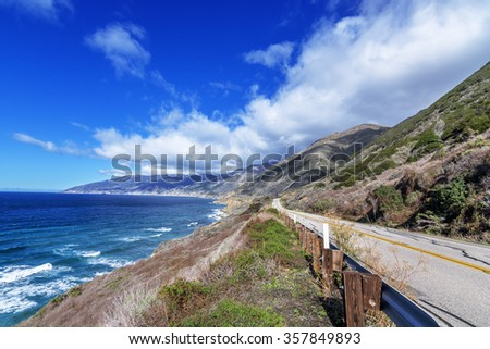 Blue sea & sky, white clouds, waves splashing on huge rocks, off shore, along a rocky coastline, desolate road to nowhere, traveling the Big Sur Highway (Highway 1) on the California Central Coast. - stock photo