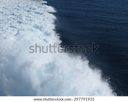 Blue sea water splash in trace of the ship - stock photo