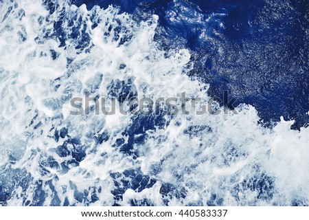 Blue sea water surface in motion with foam - stock photo