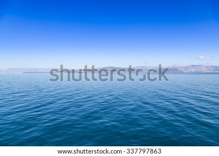 Blue sea waters and clear blue sky with distant land - stock photo