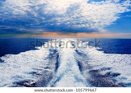 Blue sea with prop wash wake and Ibiza Island in horizon on sunrise - stock photo
