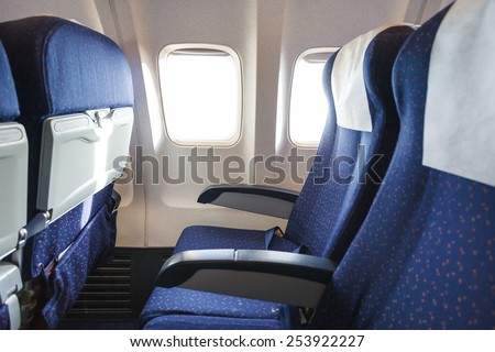 blue seats in economy class passenger section of aircraft - stock photo