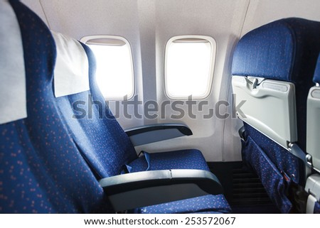 blue seats in economy class passenger section of airplane - stock photo