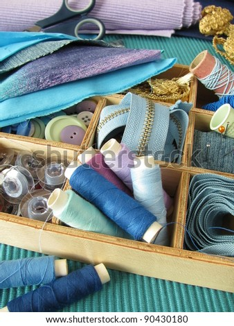Blue sewing utensils in wooden box - stock photo