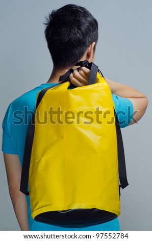 Blue shirt man carry a yellow waterproof bag - stock photo