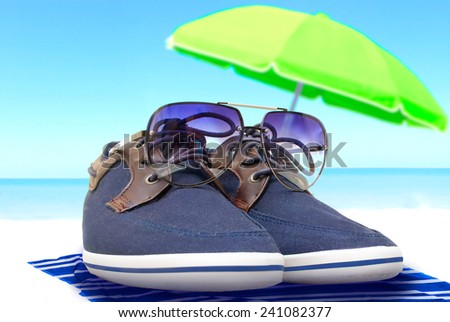 blue shoes with glasses resting on the shore under a parasol with a sea view - stock photo