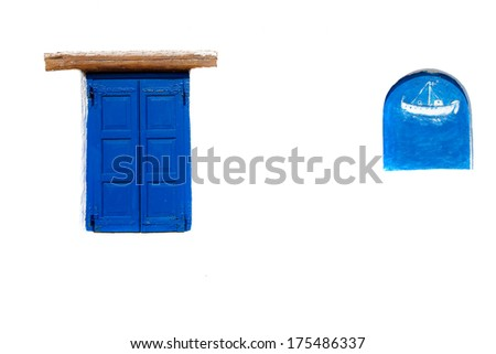Blue shuttered window on a Greek house with a decorative alcove with a picture of a ship on a traditional white-washed exterior wall - stock photo
