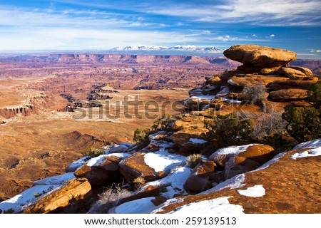Blue skies, red rocks and snow in Canyonlands National Park in Utah - stock photo