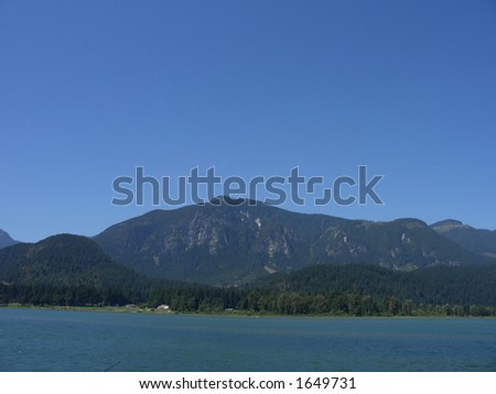 Blue sky above a clear like surrounded by mountains - stock photo