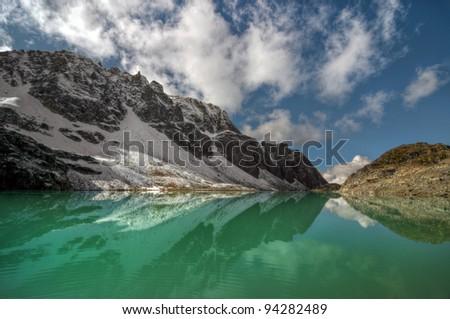 Blue sky above green mountain lake - stock photo