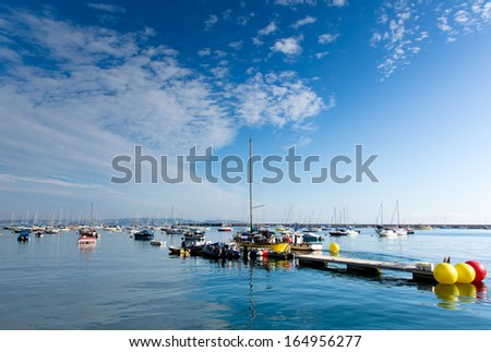 Blue sky and calm water by the yacht club Brixham harbour Devon England UK  - stock photo