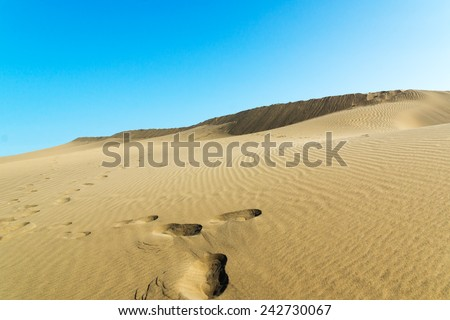Blue sky and sand dunes with footprints. Canary islands, Maspalomas. - stock photo