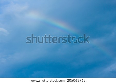 Blue sky background with rainbow - stock photo