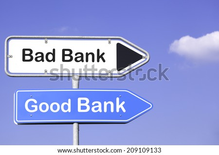 blue sky behind two white and blue road signs  on a metal mast with arrows to the right hand side showing the way to the good and bad bank.  - stock photo