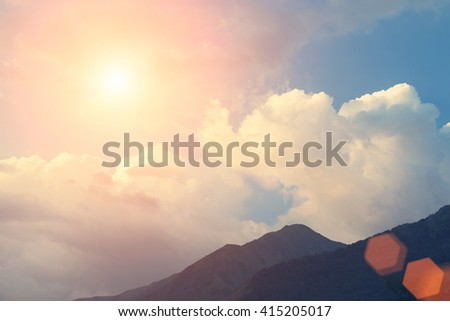 Blue sky, clouds, sun and silhouette of mountains - stock photo