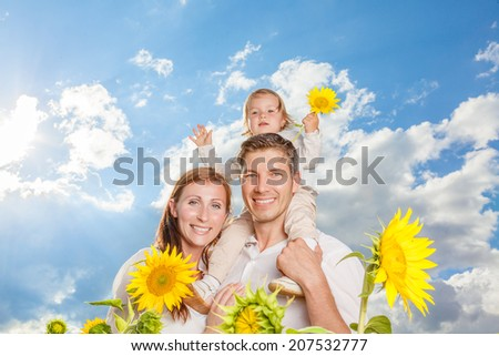 blue sky family in sunflower field - stock photo
