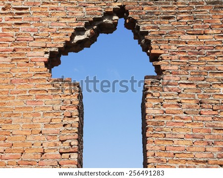 blue sky hole in brick wall background - stock photo