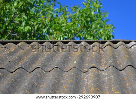 Blue sky over the dangerous asbestos old roof tiles able to use as textured background. Asbestos has not been used in domestic building materials since the 1980. - stock photo
