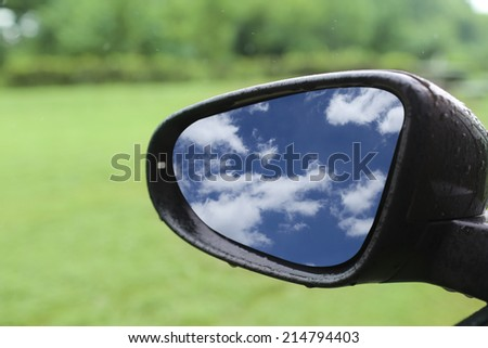 blue sky reflected in car rear mirror when driving - stock photo
