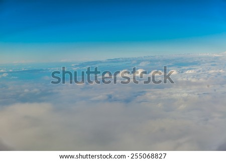 Blue sky. View from window of airplane flying in clouds. Skyscape cloudscape. Bird's eye. - stock photo