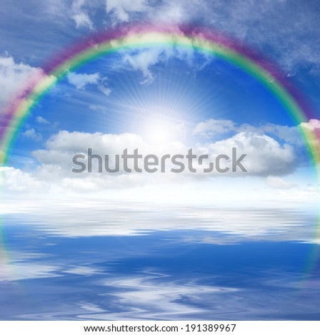 Blue sky with bright sun, rainbow and clouds, reflected in a water - stock photo
