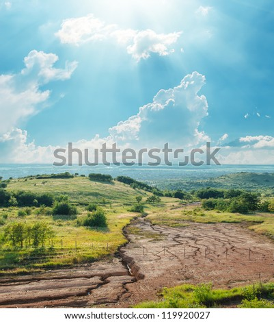 blue sky with clouds and sun over drought earth in mountains - stock photo