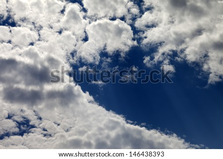 Blue sky with clouds and sunbeams - stock photo