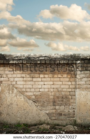 Blue sky with clouds behind the cracked wall background - stock photo