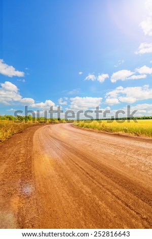 Blue sky with cumulus clouds and sunshine over the plain and country road - stock photo