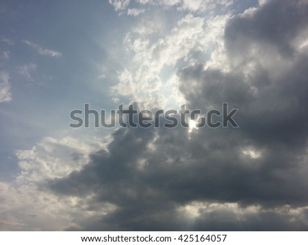Blue sky with dark clouds  and sunlight before storm - stock photo